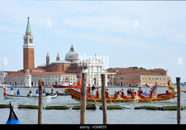 Historical boats parade befor the Island of San Giorgio Maggiore in the Lagoon of Venice in Italy. - Stock Image