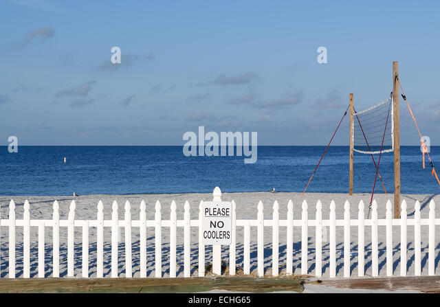 Empty beach volleyball court with net behind a picket fence on the Gulf of Mexico, Treasure Island, Florida, USA. - Stock Image