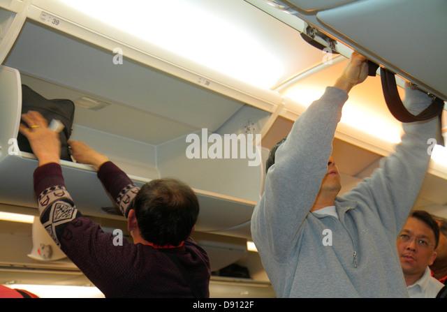 California San Francisco International Airport SFO onboard Singapore Airlines cabin boarding passengers overhead - Stock Image