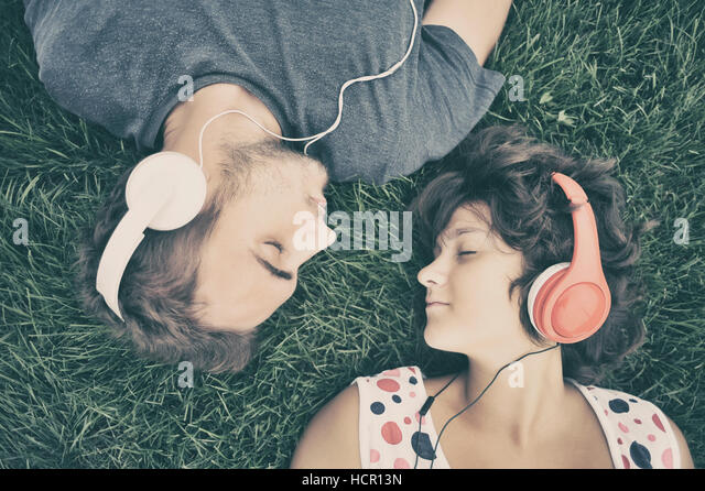 Couple listening to music on headphones - Stock Image