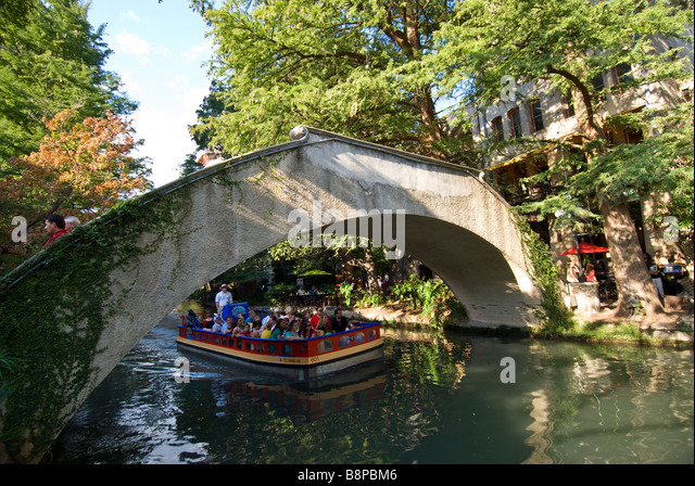 San Antonio River Walk riverwalk tour boat with tourists passes under arched bridge crossing the San Antonio River - Stock Image