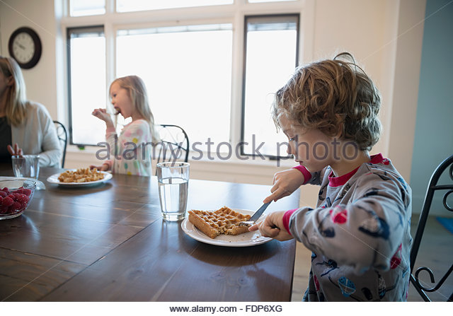 Boy eating waffle at breakfast table - Stock Image