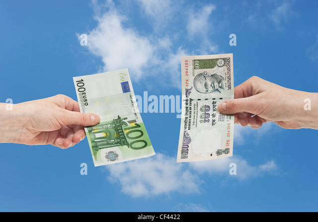 One Indian 100 rupee bill is held in the hand. At the other side a 100 Euro bill is held in the hand, background - Stock-Bilder