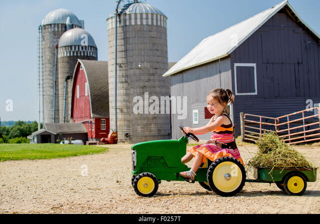 Elementary aged girl driving her toy tractor - Stock Image