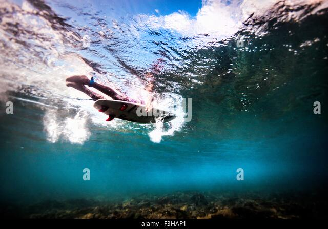 Underwater view of surfer paddling through ocean to catch waves in Bali, Indonesia - Stock Image
