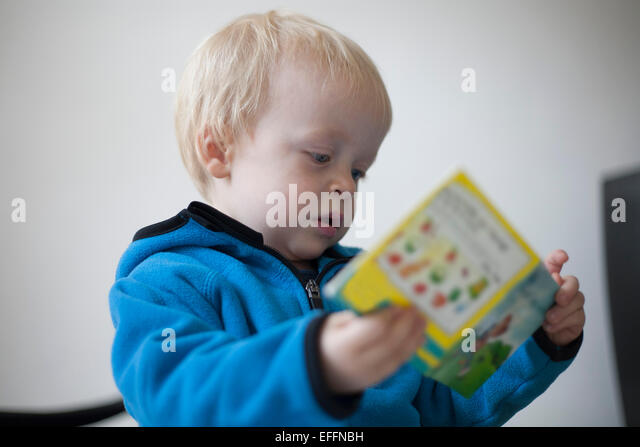 Concentrated little boy with children's book - Stock Image