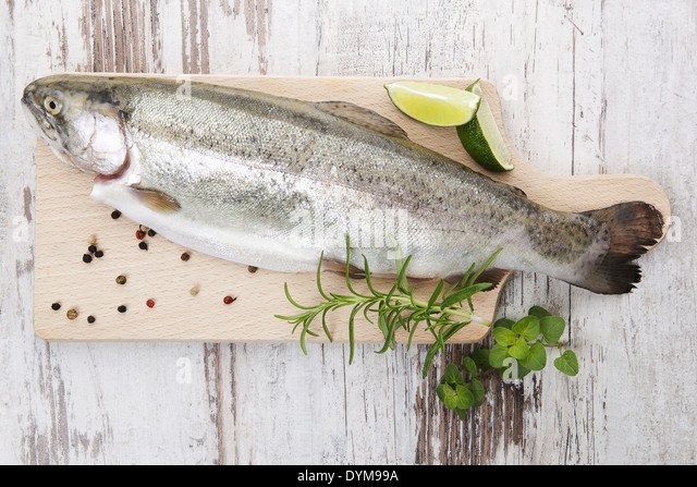 Fresh trout with pepper corns, fresh herbs and lemon on wooden kitchen board on white wooden background ready for - Stock Image
