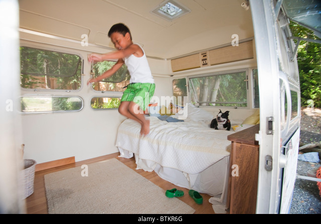 boy and dog on bed in camper - Stock Image