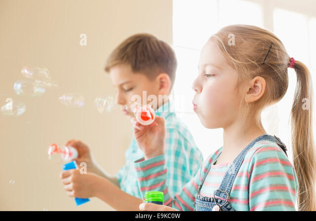 Brother and sister playing with bubble wands at home - Stock Image