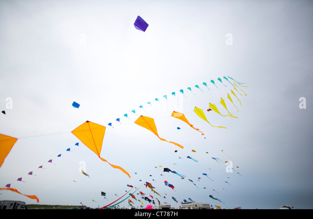 colourful kites flying in the autumn sky - Stock Image