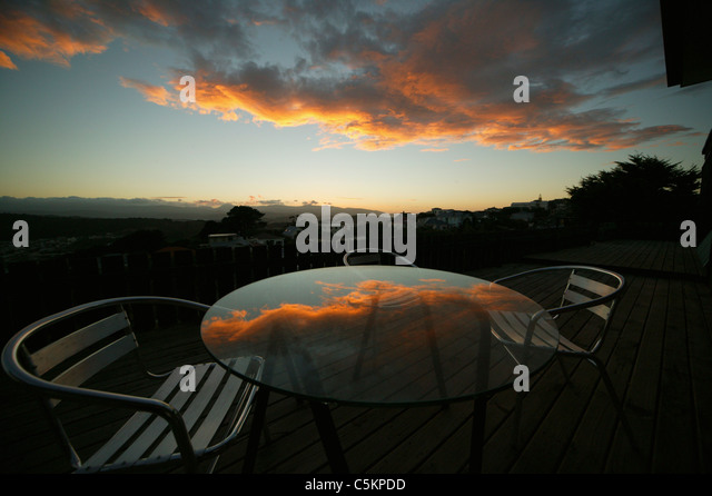 Sunrise reflected in round glass table on a deck with aluminum chairs, Wellington, New Zealand - Stock Image