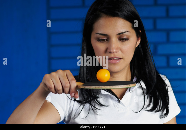 Close-up of a young woman playing with a table tennis racket and a ball - Stock Image