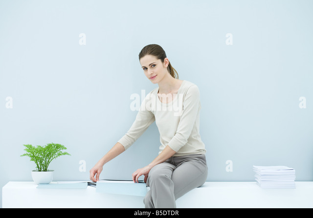 Professional woman sitting on ledge, organizing documents, smiling at camera - Stock-Bilder