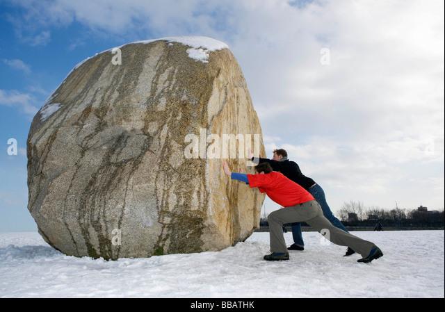 2 men pushing massive boulder - Stock Image