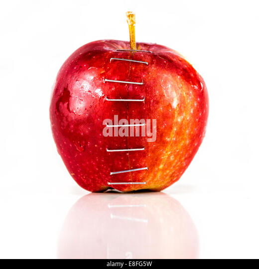 Two halves of an apple stapled together - Stock Image