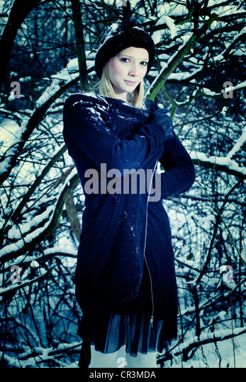 Woman standing in a wood in winter - Stock Image
