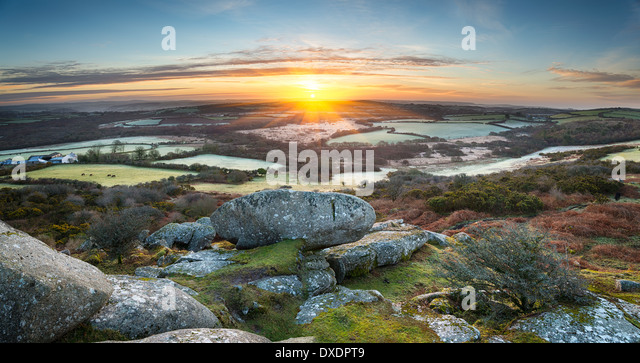 A frosty early spring sunrise looking out over a patchwork of fields and rolling hills at Helman Tor a rocky outcrop - Stock Image