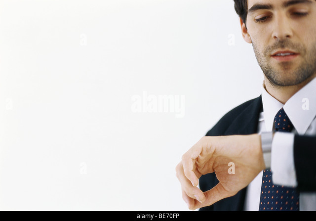 Businessman checking time, looking at watch - Stock Image