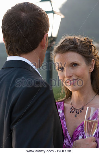 Well-dressed couple drinking champagne - Stock Image
