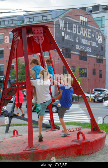 Portland Maine Historic Old Port District Commercial Street red ocean buoy boy climbing - Stock Image