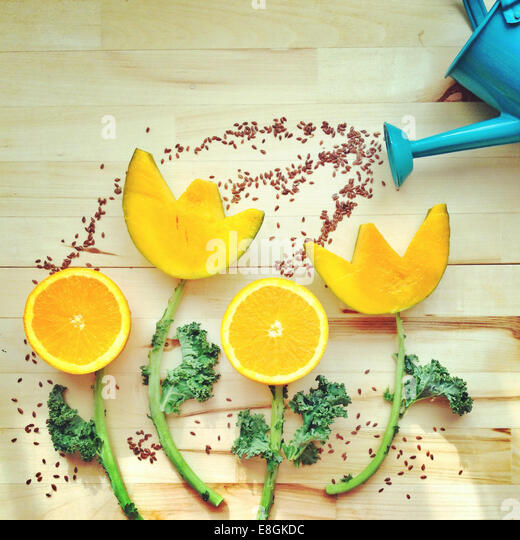 Conceptual watering can watering flowers - Stock Image