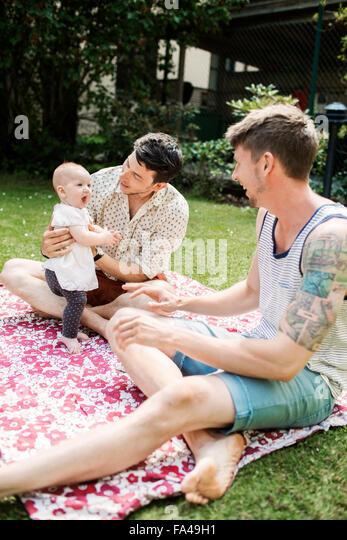 Gay couple enjoying with baby girl at yard - Stock-Bilder