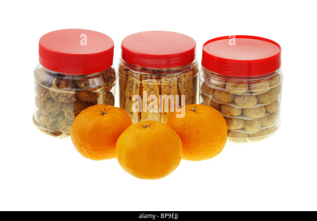 Chinese new year almond and peanut cookies with mandarin oranges on white - Stock Image