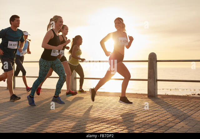 Fit young people running on street by the sea. Runners competing in a marathon race in evening. - Stock Image