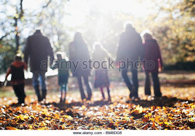 Extended family walking in park in autumn - Stock-Bilder