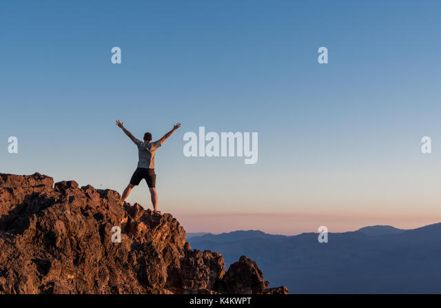 Man Stands on Rocks at Sunset on Death Valley mountain peak - Stock Image