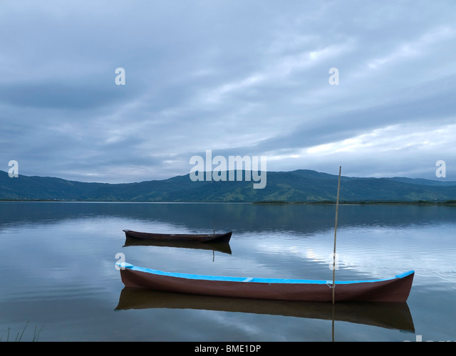 Two canoes tied on a quiet lake under a cloudy sky. - Stock Image