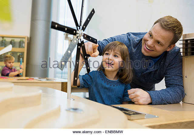 Father daughter playing metal wind turbine science center - Stock Image