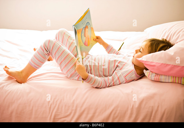 Girl, 3-5 years, lies on a cozy pink bed reading a book. - Stock Image
