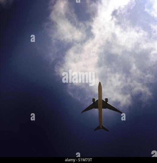 An airplane flys overhead. - Stock Image