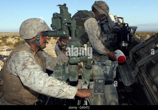 A cannoneer looks through the sights of the M777 Lightweight Howitzer as another crewman inserts a bag of gunpowder - Stock Image
