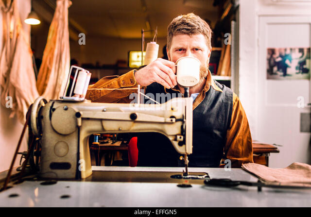 Portrait of worker having coffee while sitting at sewing machine in workshop - Stock Image