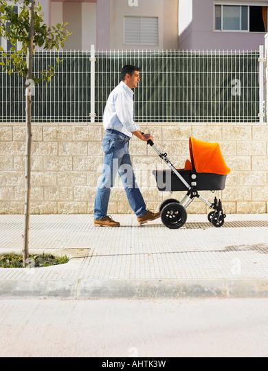 Father pushing pram on pavement, Alicante, Spain, - Stock Image