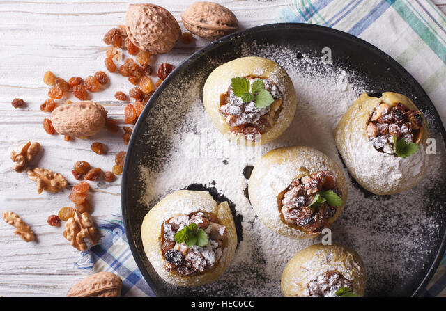 Homemade baked apples with raisins, walnuts and honey on a plate horizontal view from above closeup - Stock Image