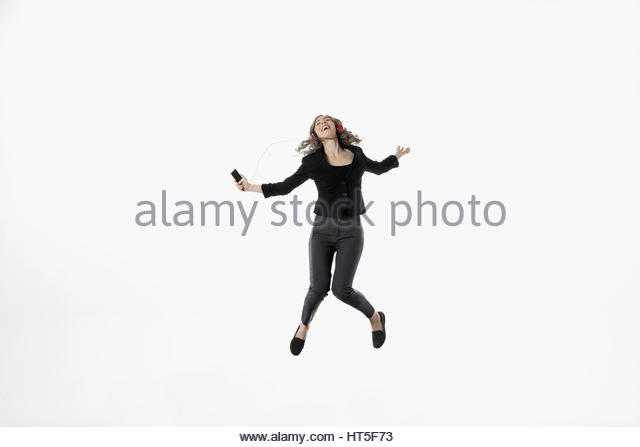 Exuberant woman jumping, listening to music against white background - Stock-Bilder