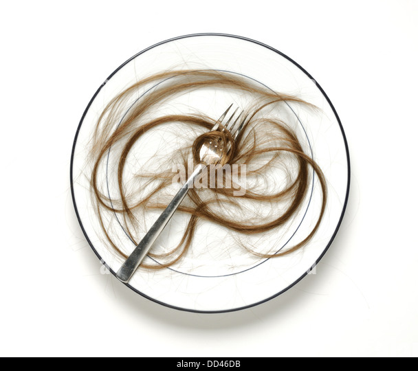 A dinning plate with a fork and many strands of human hair - Stock Image