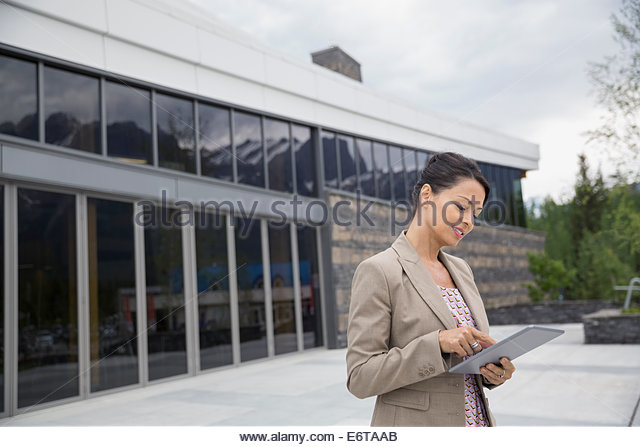 Businesswoman using digital tablet outside office building - Stock Image