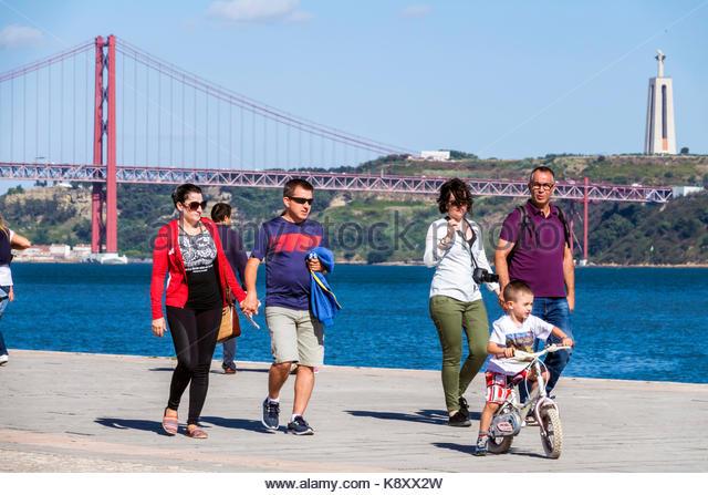 Portugal Lisbon Belem waterfront promenade Tagus River Ponte 25 de Abril 25th of April Bridge suspension tower view - Stock Image
