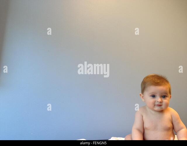 Close-Up Of Toddler Sitting Against Gray Background - Stock Image