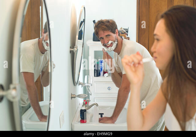 Woman brushing teeth, husband shaving - Stock-Bilder