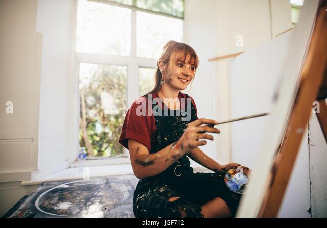 Indoor shot of female artist painting in studio. Woman painter painting in her workshop. - Stock Image