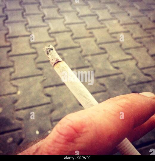 Man holding cigarette in hand - Stock-Bilder