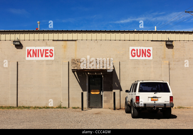 Shop selling knives and guns, New Mexico, USA (vehicle license obscured). - Stock Image