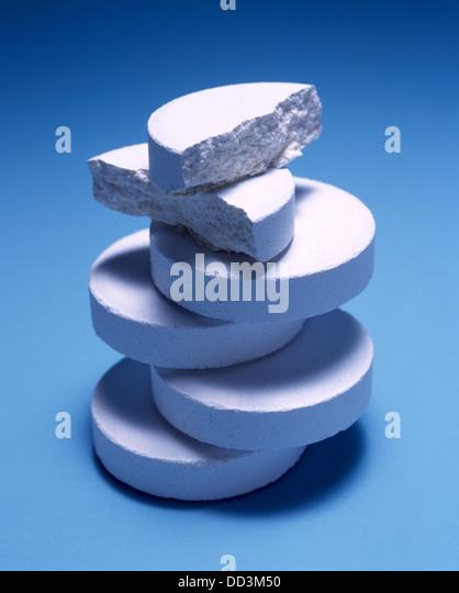 A large stack of white medicine tablets on a blue background. - Stock Image