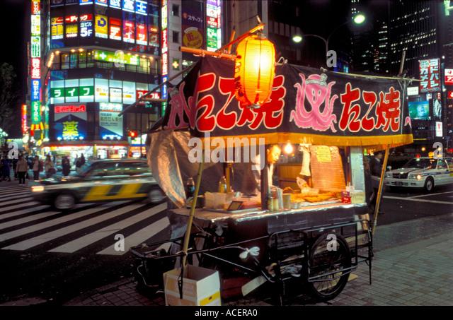 Cart selling takoyaki octopus balls on street corner in downtown Tokyo at night - Stock Image