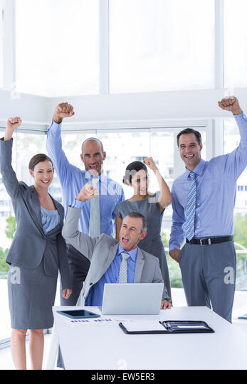 Smiling business team celebrating and looking at camera - Stock Image